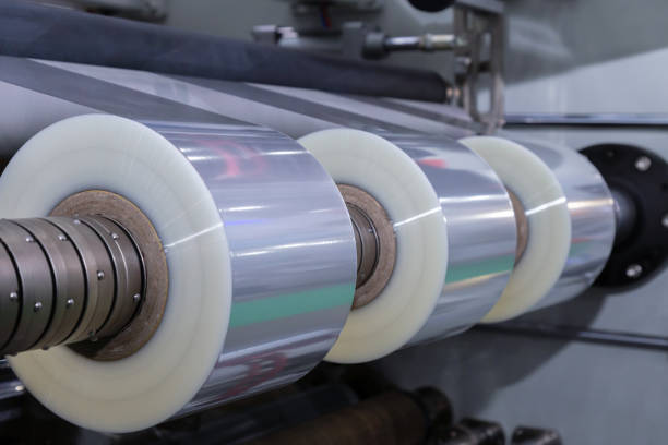 roll of plastic packaging film on the automatic packing machine in food product factory. industrial and technology concept.